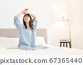 아침에 일어나 침대에서 기지개를 젊은 여성 67365440