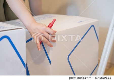 An image of a woman holding a moving cardboard, packing 67368933