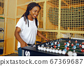 International couple playing a table football in a club 67369687