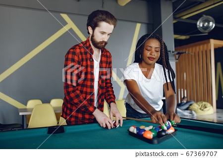 International couple playing a billiard in a club 67369707