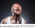 Photo of a scary mad man with maggots in his mouth 67370327