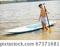 Sup surfer on a summer beach 67371681