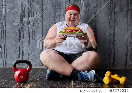 obese young man encroaches on a big sandwich 67373056
