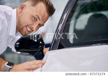 handsome caucasian man is checking the car surface 67373274