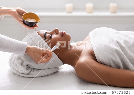 Beautician holding bowl with face mask next to black lady 67373623