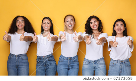 Cheerful Multicultural Girls Gesturing Thumbs-Up Posing Over Yellow Background, Panorama 67373659