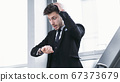 Young businessman looking at wrist watch in car 67373679