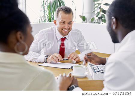 professional sales agent and clients have friendly conversation in dealership 67373854