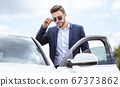Serious CEO in formal wear and sunglasses getting into his automobile at downtown area of modern city 67373862