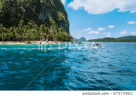Boat with tourists on ipil beach of exotic island on hopping tour, Bacuit archipelago, El Nido, Palawan , Philippines 67373962