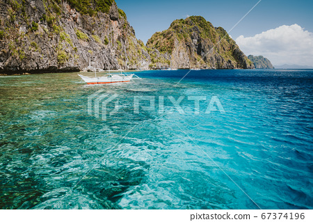 El Nido, Palawan, Philippines. Banca boat in crystal clear ocean water near Matinloc island, highlights of hopping trip on Tour C 67374196