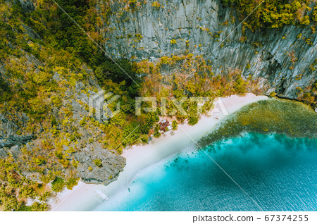 Aerial drone view of abandoned house hut on Pinagbuyutan Island in El Nido. Amazing white sand beach and emerald lagoon water 67374255