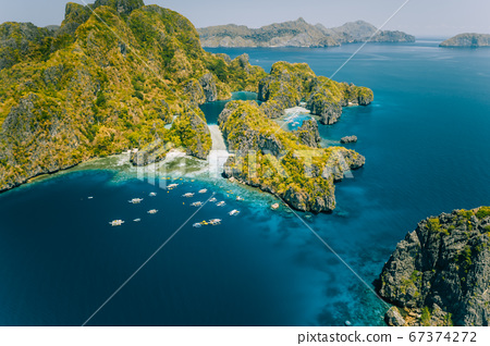 Palawan, Philippines aerial view of tropical Miniloc island. Tourism trip boats at big lagoon entrance. Natural scenery 67374272