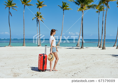 A charming woman with a red suitcase on an island 67379089