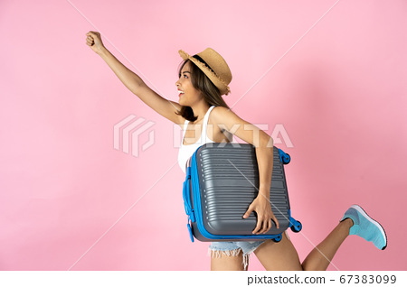 Young woman carrying suitcase with arm raised against pink background 67383099