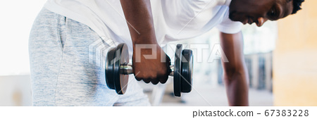 Side view of African American man in sportswear leaning on bench and doing row exercise with dumbbell during training in gym 67383228