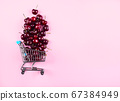 Cherries in toy shopping cart on pink background 67384949