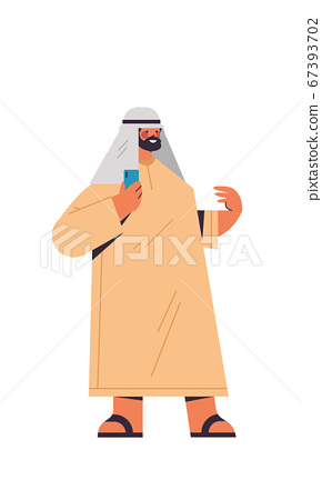 arabic man in traditional clothes arab businessman using smartphone male cartoon character standing pose 67393702