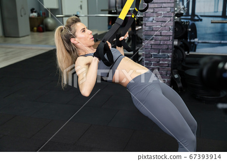 Crossfit fitness TRX training exercises at gym woman push-up workout 67393914
