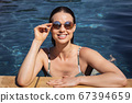 Portrait of woman with sunglasses in the pool 67394659
