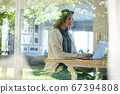 Woman using laptop while sitting near the window at home 67394808