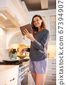 Woman using digital tablet while cooking in the kitchen 67394907