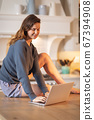 Woman using laptop in the kitchen 67394908