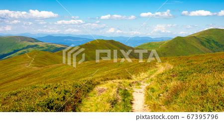 trail uphill through mountain range. grass on the 67395796
