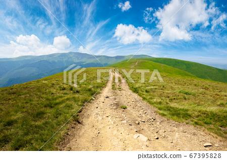 mountain road through grassy meadow. wonderful 67395828