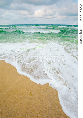 sea tide on a cloudy evening. waves crashing sandy 67395852