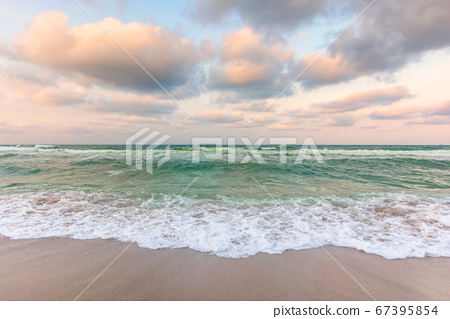 cloudy sunset sea side. waves running the sandy 67395854