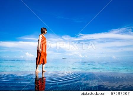 女人走在馬爾代夫無邊泳池海邊緣 67397307