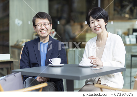 Senior couple sitting on the terrace of the cafe 67397678