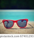 Summer background. Concept for summer and vacation. Red sunglasses by the pool in the background with blue water. 67401293