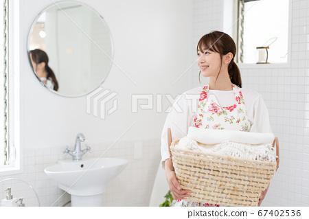 욕실에서 빨래 바구니를 안고있는 젊은 여성 67402536