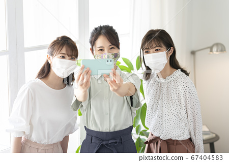 Young women wearing masks and taking selfies 67404583