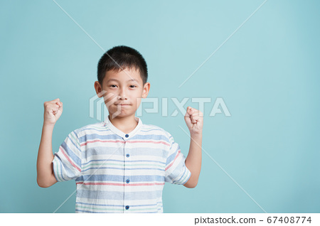 happy Asian little boy standing on blue background isolated 67408774