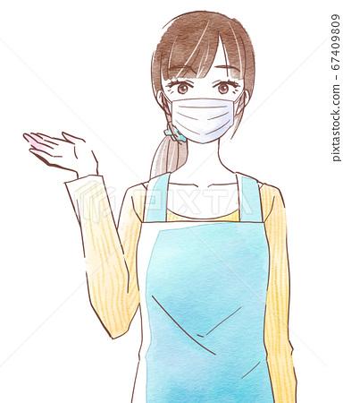一個年輕的女人,穿著圍裙和麵具,用她的右手引導 67409809