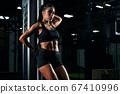 Fitnesswoman posing near gym machine. 67410996