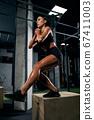 Sportswoman squatting on box in gym. 67411003