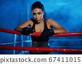 Female kickboxer having rest after training. 67411015