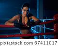 Female kickboxer having rest after fight. 67411017