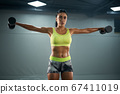 Female bodybuilder training with dumbbells. 67411019