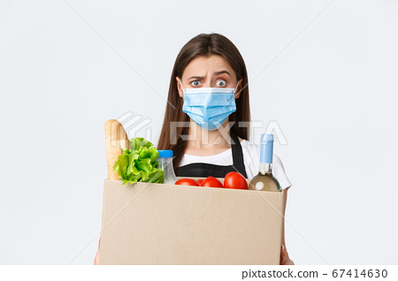 Covid-19 social distancing, delivery and grocery shopping during coronavirus concept. Confused and shocked saleswoman, cashier in medical mask raising eyebrow as holding box with groceries 67414630