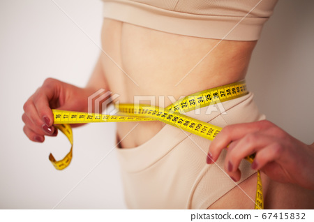 Woman with a sporty figure measures the size of her waist 67415832