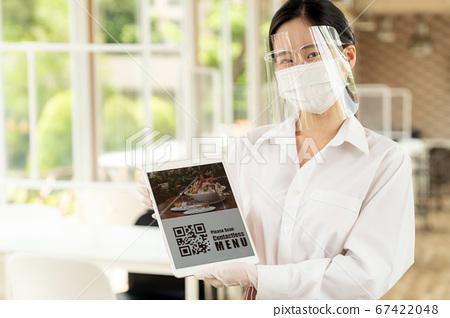 New Normal asian waitress hold qr code contactless 67422048