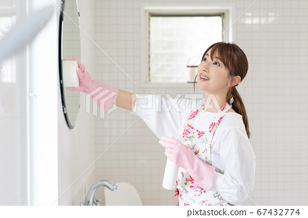 Young woman sanitizing the mirror in the bathroom 67432774