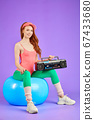 athletic female dancer sits on fit ball with portable cassette player on knees 67433680
