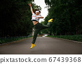 Young fitness girl jumping in dance on the road 67439368
