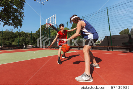 Two sportsmen playing game of basketball at outdoor court, empty space 67439985